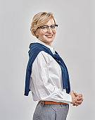 Portrait of elegant middle aged caucasian woman wearing business attire and glasses smiling at camera while posing, standing isolated over grey background