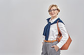 Portrait of elegant middle aged caucasian woman wearing business attire and glasses smiling at camera while posing with handbag, standing isolated over grey background
