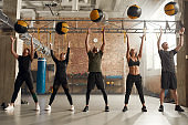Enhance your Health. Full length shot of sportive people in black sportswear using exercise ball while having workout at industrial gym. Group training, teamwork concept