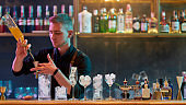 Young male bartender pouring, mixing ingredients while making classic cocktail alcoholic drink at the bar counter in the night club