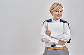 Portrait of elegant middle aged caucasian woman wearing business attire holding laptop, smiling at camera while posing isolated over grey background