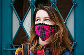 Closeup portrait of a young woman wearing a plaid handmade face mask on old blue door background