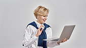 Portrait of elegant middle aged caucasian woman wearing business attire holding laptop, while having online video call, standing isolated over grey background