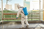 Save a life. Sanitization, cleaning and disinfection of the city due to the emergence of the Covid19 virus. Man in protective suit and mask at work near the bus stop
