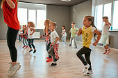 Studying modern dance. Group of little boys and girls dancing while having choreography class in the dance studio. Female dance teacher and children dancing