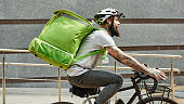 Food at anytime. Bearded delivery man in helmet with full thermo bag or backpack riding a bike along the city, delivering food. Courier, delivery service concept