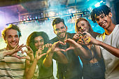 Nightclub time. Young men and women showing heart signs while posing together for camera. Multiracial group of friends hanging out at party in the bar