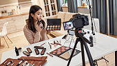 You will love it. Beauty blogger woman filming, advertising app on camera, holding smartphone. Makeup influencer asian girl recording cosmetics product review at home