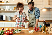 Time for pizza. Young couple in love preparing the dough for making pizza with vegetables at home. Man and woman wearing apron, cooking together indoors. Hobby, lifestyle