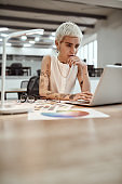 Successful businesswoman. Pretty and young tattooed female designer using laptop while working at her desk in the modern office. Designer workplace