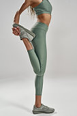 Effective warmup. Vertical shot of a fitness woman in sportswear stretching her legs before workout while standing isolated over grey background