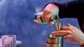 Close up of hands of male bartender pouring, mixing ingredients while making cocktail alcoholic drink at the bar counter in the night club