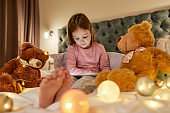 A cute girl wearing pyjamas sitting alone on a huge bed barefoot watching cartoons on a tablet before going to sleep with her fluffy toys and garlands all over the bed