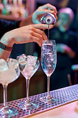 Close up of hands of male bartender pouring, mixing ingredients while making classic cocktail alcoholic drink at the bar counter in the night club