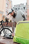 Everything for you. Brutal stylish delivery man opening thermo bag or backpack to take food out, standing outdoors with bike. Courier, delivery service concept