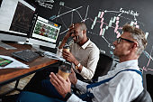 Earn better. Two diverse colleagues traders discussing ideas while sitting in the office in front of multiple computer screens. Blackboard full of charts and data analyses in the background.