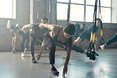 Fitness Center. Portrait of men and women doing fitness training exercises at industrial gym. Straps, group workout concept