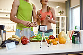 Sharing ideas. Cropped shot of couple recording video blog or vlog about healthy nutrition at home. Man and woman showing ingredients and explaining how to cook a dish, standing in the kitchen