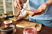 Close up of man spreading pink beet hummus onto toasted bread. Couple of vegetarians preparing healthy meal in the kitchen together. Vegetarianism, healthy food concept