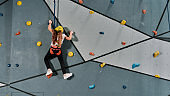 Girl in safety equipment and harness training on the artificial climbing wall indoors. Bouldering training concept