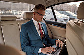Setting goals. Serious mature businessman in full suit working on his laptop while sitting in the car