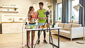 Gain a passion. Young couple recording video blog or vlog about healthy nutrition on camera at home. Man and woman showing how to prepare smoothie, standing in the kitchen