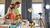Creating Valuable Moments. Sportive couple recording video blog or vlog about healthy nutrition on camera at home. Man and woman showing fruits that they consume, standing in the kitchen