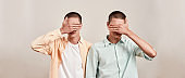 Two caucasian men, twin brothers covering eyes with hand while posing together isolated over beige background, panoramic banner