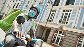 On my way. Delivery man in helmet wearing mask due to the emergence of the Covid19 virus, riding a motor scooter, delivering food. Courier, delivery service, lockdown concept