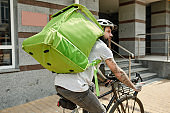Food travelled for you. Bearded delivery man in helmet with full thermo bag or backpack looking aside, riding a bike along the city, delivering food. Courier, delivery service concept