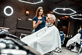Making stylish hairstyle in barber shop. Side view of young professional barber girl using hair clipper. She is making new haircut for elegant mature man sitting in armchair in the front of mirror