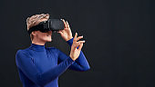 Woman with short hair in blue turtleneck wearing virtual reality headset, vr glasses isolated over dark background