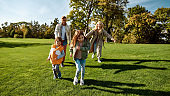Sunny day. Excited family running outdoors on a sunny day