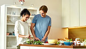 Young man cutting vegetables while woman tossing a salad. Vegetarians preparing healthy meal in the kitchen together. Vegetarianism, healthy food concept