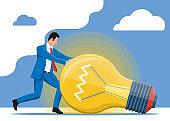 Businessman pushing big light idea bulb.