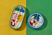 Top view of containers for pills with different medicines. Pill organizer box storing doses of daily medicine on yellow, green background