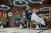 Man visiting barbershop. Side view of professional barber is drying hair of his young client who is sitting in chair in front of a mirror in the barbershop