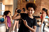 African american boy showing muscle while exercising using dumbbell in gym together with female trainer and other kids. Sport, healthy lifestyle, physical education concept