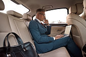 Perfect productivity. Side view of handsome mature businessman in full suit working on his laptop while sitting in the car