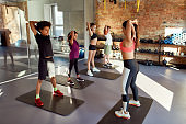Every day is a workout. Full-length shot of female trainer warming up, exercising with teens, boys and girls in gym. Stretching on a sunny day. Sport, healthy lifestyle, physical education concept