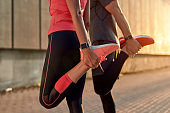 Staying flexible. Cropped photo of fitness couple in sports clothing doing stretching exercises together outdoors