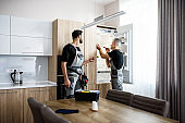 Adding care to your technologies. Aged repairman in uniform fixing refrigerator in the kitchen, while his colleague helping him, bringing screwdriver. Repair service concept