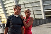 We Love Sport. Portrait of happy middle-aged couple in sport clothing looking away with smile while training together outdoors