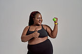 Plump, plus size african american woman in sportswear showing thumbs up while exercising, holding green dumbbell in studio over grey background