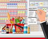 Supermarket interior with goods hand with receipt.