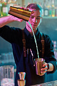 Bartender do it better. Close up of male bartender pouring, mixing ingredients while making cocktail alcoholic drink at the bar counter in the night club