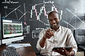 Just earn more. Cheerful african american male trader sitting by desk, pointing at camera and studying analytical reports using tablet pc in the office