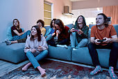 Teenagers smoking and having fun. Group of young multicultural people playing video games and smoking marijuana from a bong while sitting on the couch at home