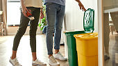 Put trash in its place. Young couple in casual clothes sorting garbage while cleaning their kitchen together. Cleaning home, recycling, housework, family life concept