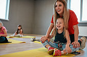 Training a little child. Portrait of a cheerful female trainer helping cute little girl to do butterfly exercise. Group of children sitting on the floor and stretching muscles